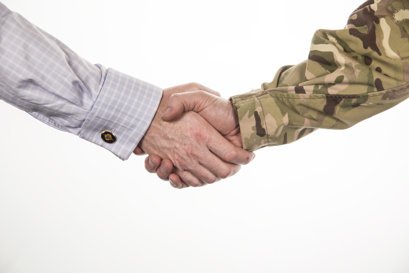 Male civilian and male serviceman shaking hands.